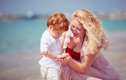 Happy mother with baby son playing with pebble stones on the beach, summer vacation Royalty Free Stock Photos