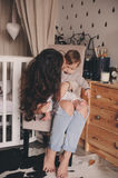 Happy mother and baby son playing together at home. Happy family lifestyle concept in real life interior. Happy mother and baby son playing together at home Royalty Free Stock Photos