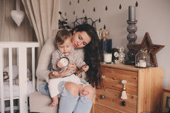Happy mother and baby son playing together at home. Happy family lifestyle concept in real life interior. Happy mother and baby son playing together at home Stock Photography