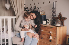 Happy mother and baby son playing together at home. Happy family lifestyle concept in real life interior Stock Images