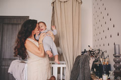 Happy mother and baby son playing together at home, mom holding and kissing her 11 month old boy Stock Photo