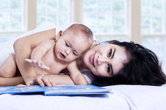 Happy mother and baby with a story book. At home Stock Image