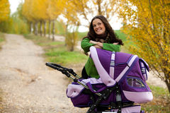 Happy mother with baby in stroller Royalty Free Stock Images