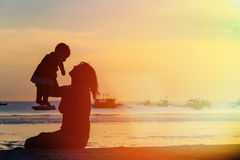 Happy mother and baby at sunset beach Royalty Free Stock Images