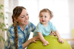 Happy mother and baby boy on fitness ball in nursery at home. Gimnastics for kids on fitball. Happy mother and baby toddler on fitness ball in nursery at home Royalty Free Stock Images