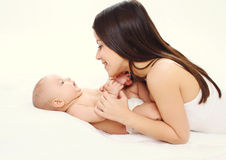 Happy mother and baby together lying on bed Stock Image