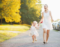 Happy mother and baby walking in city Stock Photo