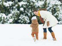 Happy mother and baby walking outdoors in winter Stock Photo