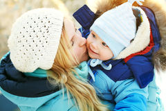 Happy mother and baby in winter park Stock Image