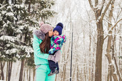 Happy mother and baby in winter park. family outdoors. cheerful mommy with her child Royalty Free Stock Images