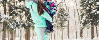 Happy mother and baby in winter park. family outdoors. cheerful mommy with her child Royalty Free Stock Image