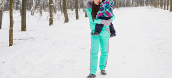 Happy mother and baby in winter park. family outdoors. cheerful mommy with her child Royalty Free Stock Photo