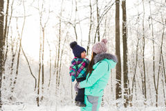 Happy mother and baby in winter park. family outdoors. cheerful mommy with her child Royalty Free Stock Photos