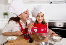 Happy mother baking with little daughter in apron and cook hat with flour dough at kitchen Royalty Free Stock Image
