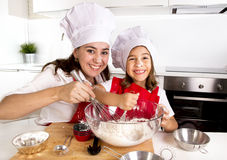Happy mother baking with little daughter in apron and cook hat with flour dough at kitchen Royalty Free Stock Photography