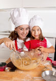Happy mother baking with little daughter in apron and cook hat preparing dough at kitchen Royalty Free Stock Photography