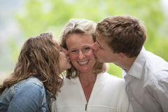 Happy mother being kissed by daughter and son. A happy smiling and laughing mother being kissed by her teenage daughter and teenage son Stock Image