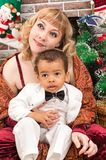 Happy mother and black baby boy cuddling by fireplace. Christmas Stock Photos