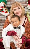 Happy mother and black baby boy cuddling by fireplace. Christmas Stock Image