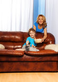 Happy mother and boy watching TV program together Stock Photos