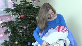 Happy mother breastfeed feed infant baby near Christmas tree