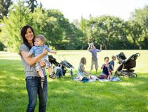 Happy Mother Carrying Baby Boy At Park. Portrait of happy mother carrying baby boy with friends and children in background at park Stock Photo