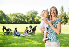 Happy Mother Carrying Daughter In Park Stock Photo