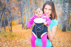 Happy mother carrying her child by ergonomic baby carrier Stock Photo