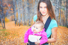 Happy mother carrying her child by ergonomic baby carrier Royalty Free Stock Photos
