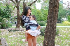 Happy mother carrying her daughter in garden with fully fall pink flower around. Happy loving family stock photography