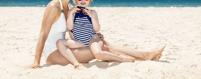 Happy mother and child at beach looking on photos in camera. Family fun on white sand. Happy mother and child in swimsuits at sandy beach on a sunny day looking stock illustration