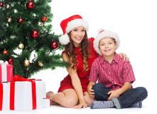 Happy mother and child boy with gift boxes. Holidays, presents, christmas, x-mas concept - happy mother and child boy in santa helper hats with gift boxes royalty free stock images