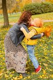 Happy Mother and Child Boy Hugging in Fall Park Stock Image