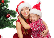 Happy mother and child boy in santa helper hats. Holidays, presents, christmas, x-mas concept - happy mother and child boy in santa helper hats royalty free stock images