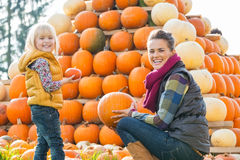 Happy mother and child choosing pumpkins Stock Images