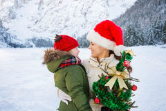 Happy mother and child with Christmas tree in front of mountains Royalty Free Stock Photos