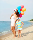 Happy mother and child with colorful balloons walking on beach Stock Image