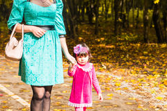 Happy mother and child daughter holding hands together in summer or autumn day. Royalty Free Stock Photo