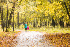 Happy mother and child daughter holding hands together in summer or autumn day. Stock Photos