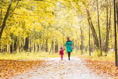 Happy mother and child daughter holding hands together in summer or autumn day. Stock Photography