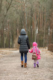 Happy mother and child daughter holding hands together walking in spring park Stock Photos