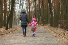 Happy mother and child daughter holding hands together walking in spring park. Outdoors Stock Photography