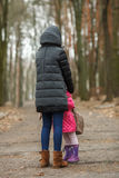 Happy mother and child daughter hugging at spring park path. Outdoors Stock Images