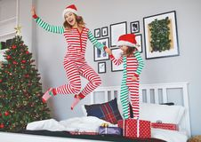 Happy mother and child daughter in pajamas jumping in bed on chr royalty free stock images