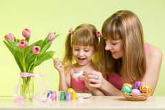 Happy mother and child daughter prepare to Easter holiday with brush coloring eggs. Mother and child daughter preparing to Easter holiday and with brush coloring Royalty Free Stock Photo