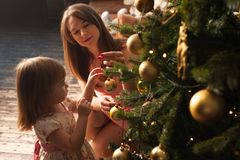 Happy mother and child decorating Christmas tree. Happy smiling mother and little daughter decorating Christmas tree together. Loving parent and child having fun Royalty Free Stock Images