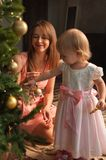 Happy mother and child decorating Christmas tree. Happy smiling mother and little daughter decorating Christmas tree together. Loving parent and child having fun Stock Images
