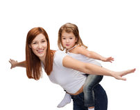 Happy mother and child doing piggy back. Childhood and parenting concept - happy mother and child doing piggy back Royalty Free Stock Photography
