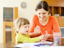 Happy mother and  child drawing  with hands and watercolor Stock Photos