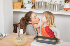 Happy mother and child when finishing cake royalty free stock photography